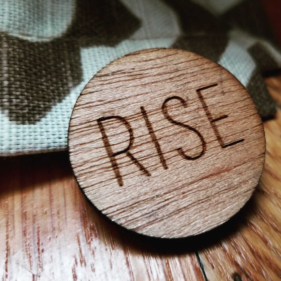 "Photo of a brown wooden pin atop a brown and cream patterned textile. The pin says, ""Rise."""