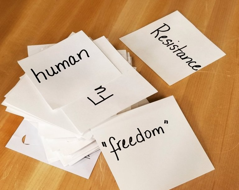 """Notecards spread out on a wooden floor. The cards say, """" human, freedom, resistance."""""""
