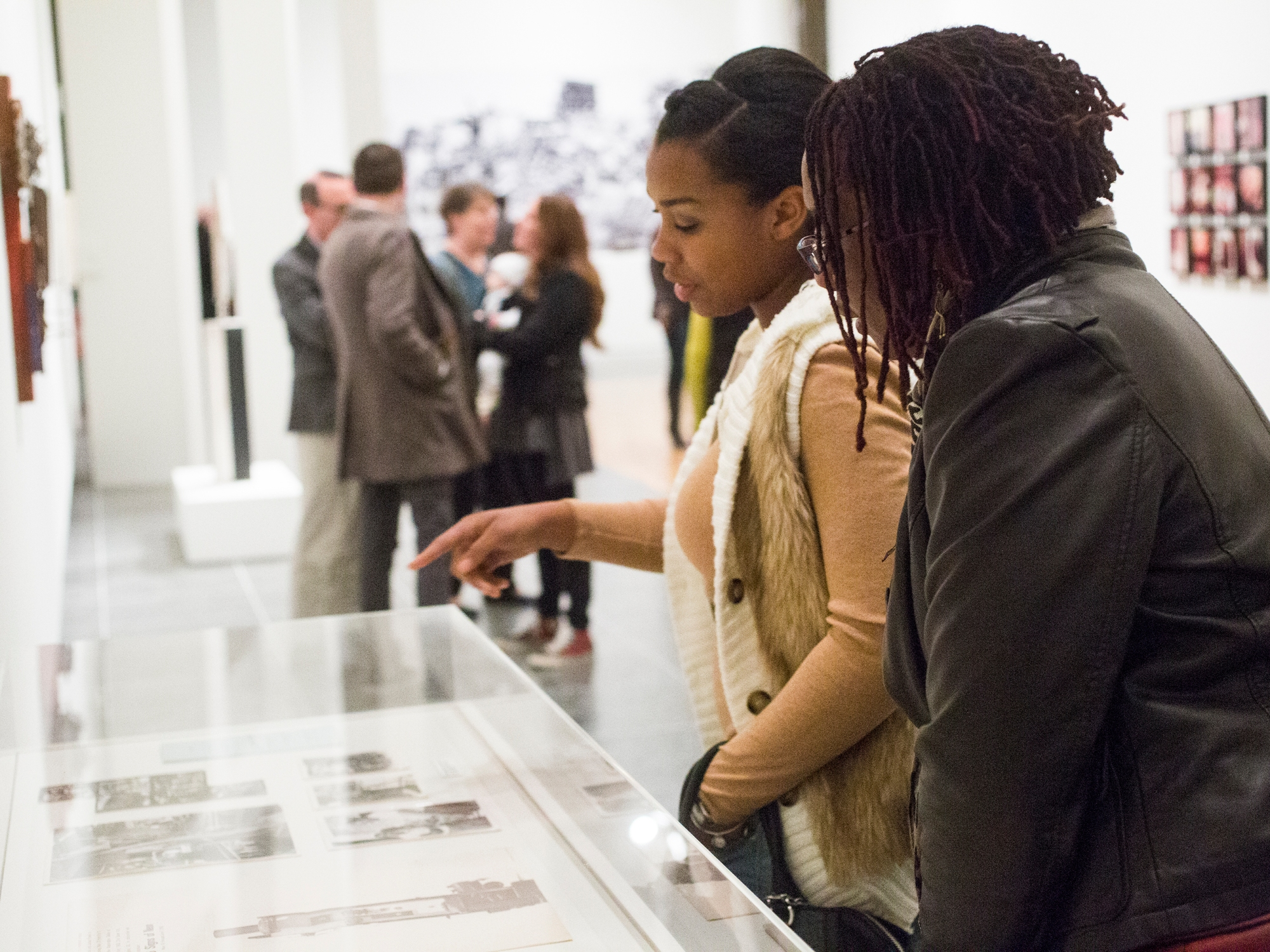Two museum visitors looking down at photos in a plexiglass display case.