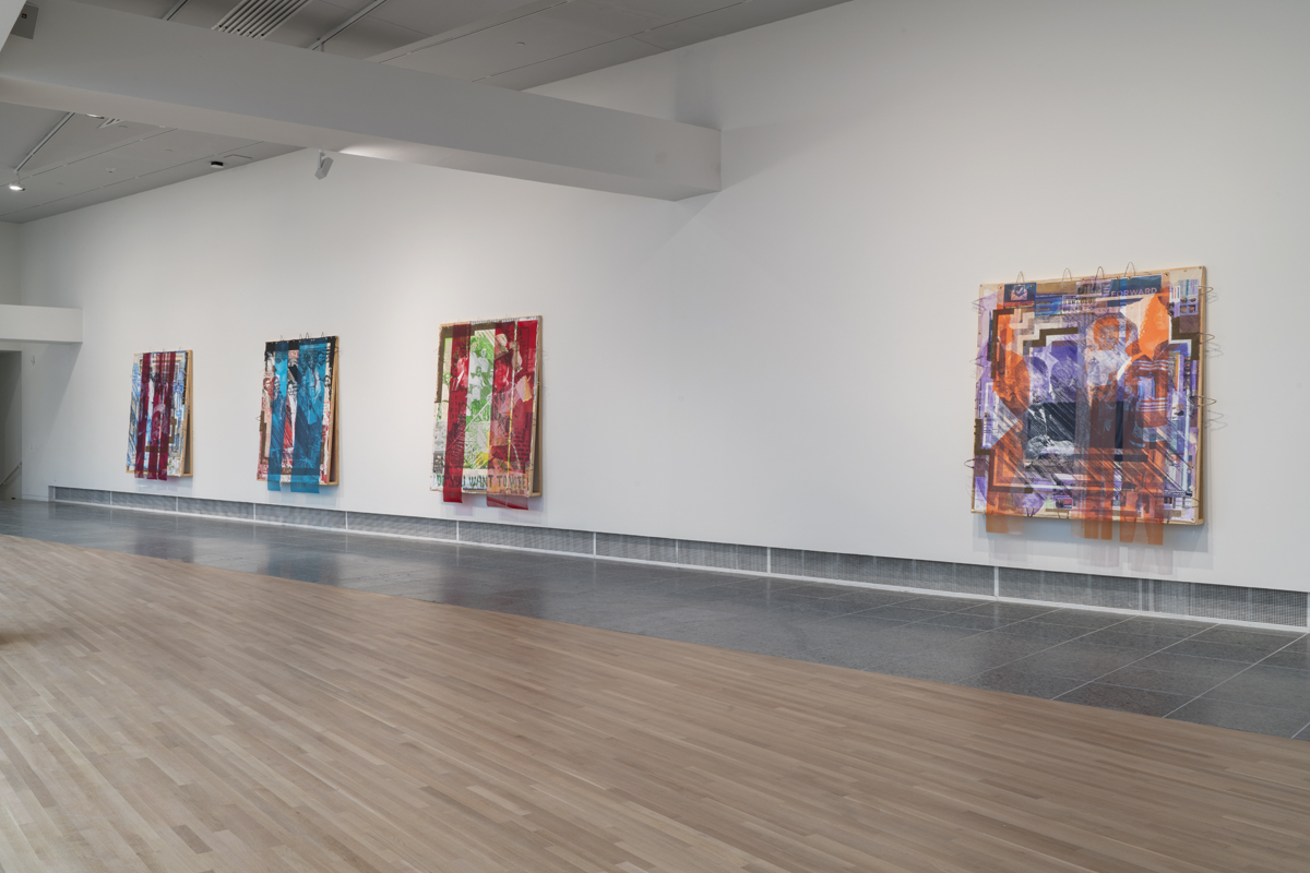 Four large mixed media paintings hanging on the wall in a gallery.